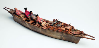 Model of an umiak, or women's boat, with four female rowers and a steersman, West Greenland 1900-1920